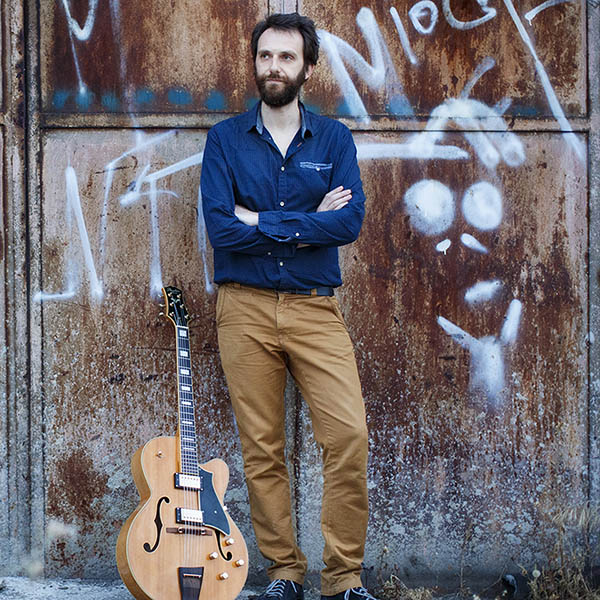 Andreas Papagiannakopoulos standing in front of a rusty iron door with his guitar by him.