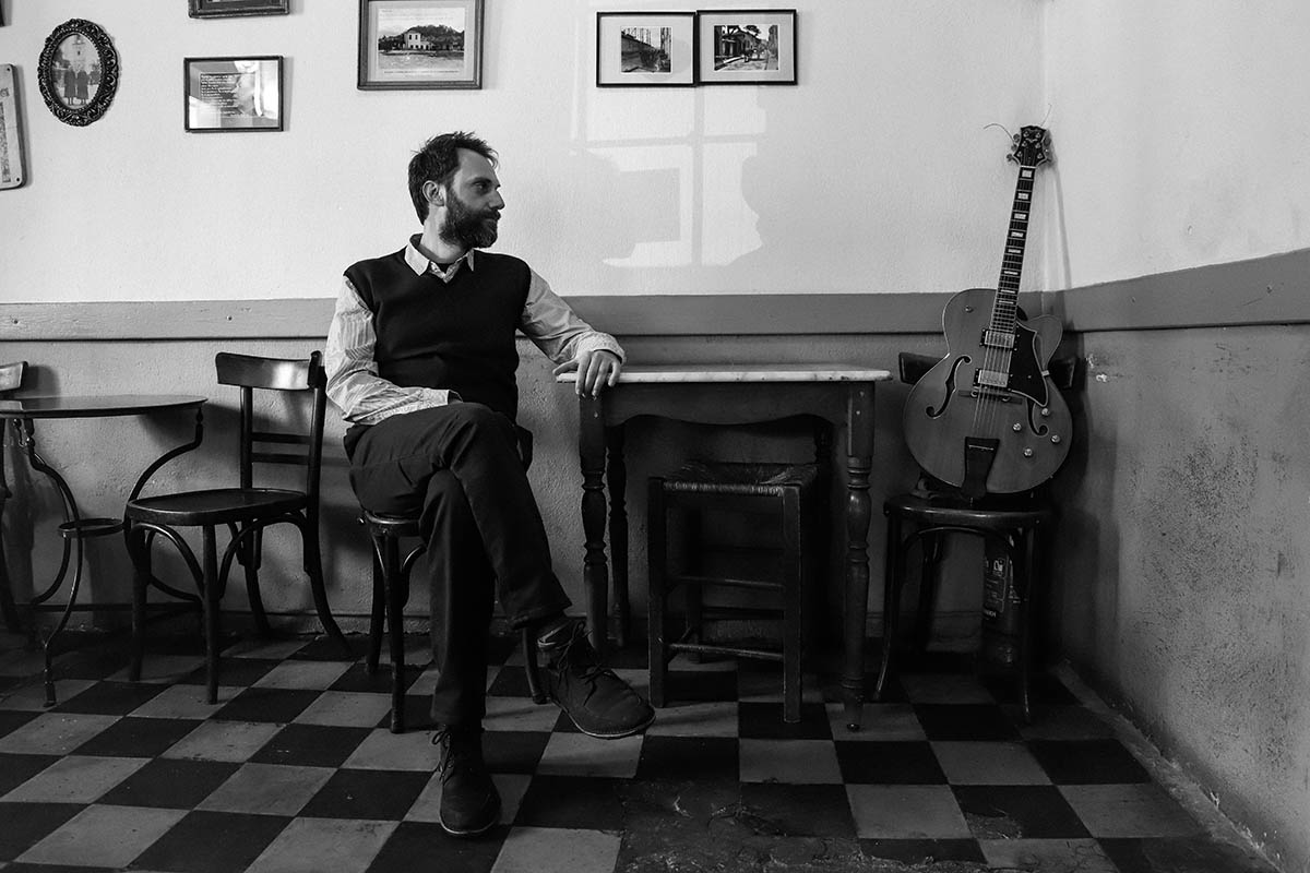 Andreas Papagiannakopoulos sitting on a chair looking at his guitar